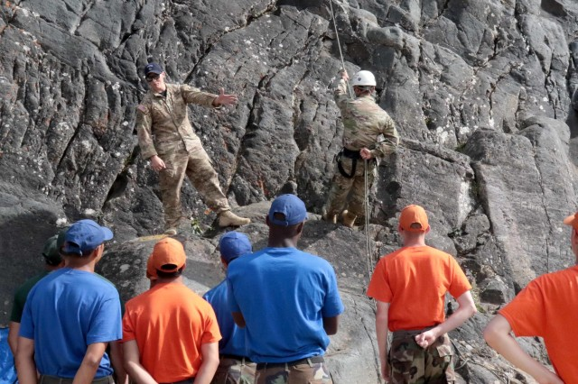 Staff Sgt. Jack Stacy, an operations NCO and former mountaineering instructor with the Northern Warfare Training Center, U.S. Army Alaska, and Staff Sgt. Christian Logtu, an NWTC instructor, explain to cadets in Ben Eielson High School's Junior Reserve Officer Training Corps, how to rappel down a cliff face during the program's Summer Leadership Camp. The mountaineering familiarization course was just one day of an eight-day camp.