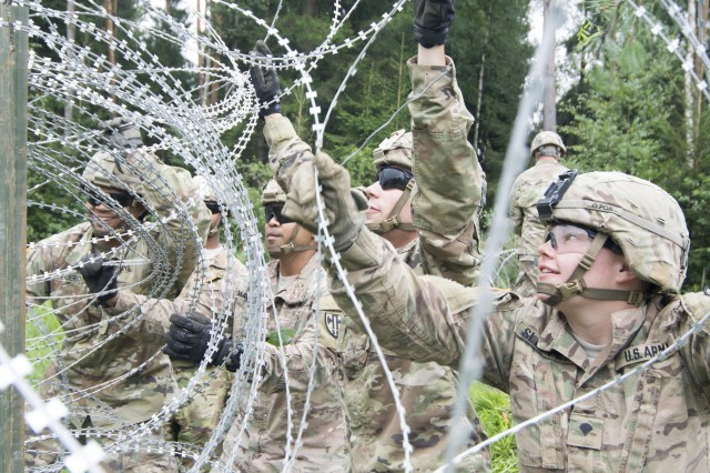 Spc. Justino Peguero, Sgt. Chrisreal Matarlo, Spcs. William Mafioletti and Chelsea Slappey, all from the 902nd Engineer Construction Company, 15th Engineering Battalion in Grafenwoehr, Germany, wrap concertina wire where trees tore down fencing in the training area. The Soldiers were part of the engineering team that worked alongside garrison and German organizations to make repairs across the installation after Thursday's storm at Rose Barracks, U.S. Army Garrison Bavaria.