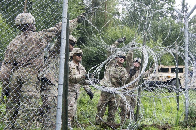 Spcs. Kelsey Bible, Justino Peguero, SGT Chrisreal Matarlo, Spcs. William Mafioletti and SPC Chelsea Slappey, 902nd Engineer Construction Company, 15th Engineering Battalion, pull the concertina wire across existing fence lines to create a new barrier. The U.S. Army Garrison Bavaria crisis action team called the engineer platoons the morning following a microburst thunderstorm at Rose Barracks to assist with the community-wide cleanup.