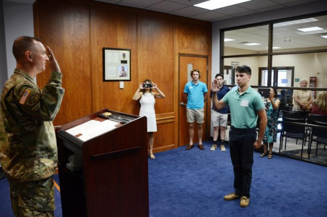Col. James Ring, chief of staff for the Virginia National Guard, enlists Pvt. Paul David Kelly into the Virginia National Guard July 26, 2017, at Fort Lee, Virginia. Kelly is the son of fallen Virginia National Guard Soldier Col. Paul M. Kelly, who was killed in a helicopter crash in Iraq in 2007.