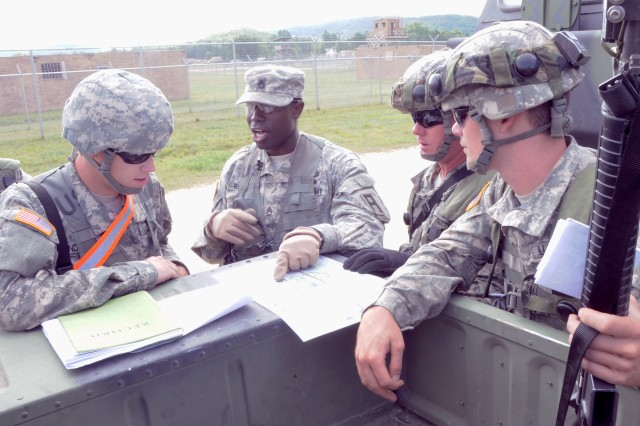 Sgt. 1st Class Anthony Baggett, center, an observer coach/trainer with First Army Division West's 181st Infantry Brigade, talks with Soldiers of the Army Reserve's 282nd Quartermaster Company from Montgomery, Ala., about their plans for executing a convoy during a Combat Support Training Exercise at Fort McCoy, Wis., on Aug. 11.