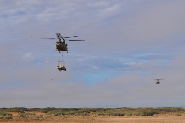 A CJ-47 Chinook transports a Warfighter Information Network-Tactical (WIN-T) Network Operations and Security Center-Lite (NOSC-L) during the Tactical Communication Node-Lite and NOSC-L operational test, held with Network Integration Evaluation 17.2, at Fort Bliss, Texas, on July 24, 2017.