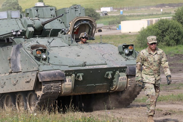 A Soldier from the 1st Battalion, 66th Armor Regiment, 3rd Armored Brigade Combat Team, 4th Infantry Division, guides an M2A3 Bradley fighting vehicle to a maintenance area on July 1, 2017, at the Cincu Joint Multinational Training Center in Cincu, Romania