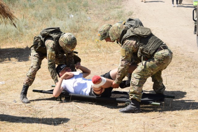 Kazakhstani soldiers with the Kazakhstan Peacekeeping Battalion place a casualty on a stretcher as part of a simulated field training exercise Aug. 1, 2017, during Exercise Steppe Eagle 17 at Illisky Training Center near Almaty, Kazakhstan.