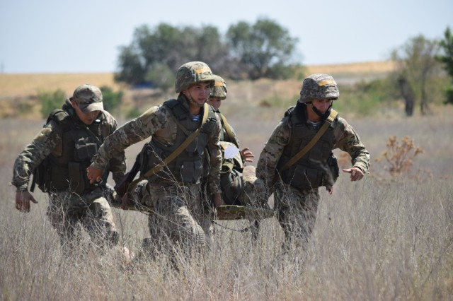 Four Kazakhstani soldiers with the Kazakhstan Peacekeeping Battalion quickly carry a simulated casualty to a helicopter for medical evacuation during a field training exercise Aug. 1, 2017, for Exercise Steppe Eagle 17 at Illisky Training Center near Almaty, Kazakhstan.