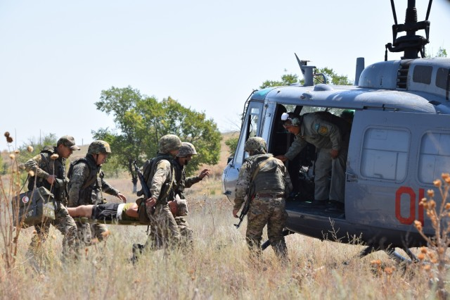 Four Kazakhstani soldiers with the Kazakhstan Peacekeeping Battalion load a simulated casualty into a helicopter for medical evacuation during a field training exercise Aug. 1, 2017, for Exercise Steppe Eagle 17 at Illisky Training Center near Almaty, Kazakhstan.