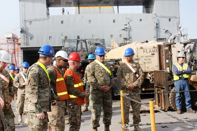 Maj. Gen. Les Carroll, the commander of the 377th Theater Sustainment Command, Col. Lillard Evans, 595th Transportation Brigade commander, and members of the 840th Transportation Battalion watch as equipment is loaded onto the USNS Mendonca at the Port of Shuaiba, Kuwait, on March 3, 2017.