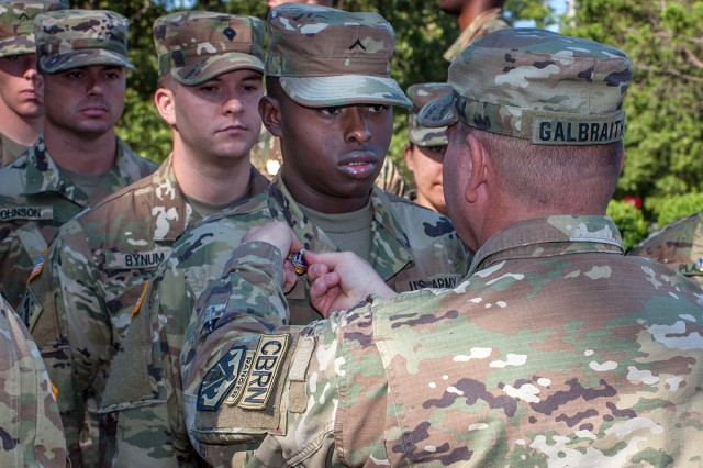 Pvt. Jah'marius Chisolm-Murray gets his Chemical Corps crest pinned to his collar by Lt. Col. Bryon Galbraith, 84th Chemical Battalion commander, during the Company B induction ceremony.