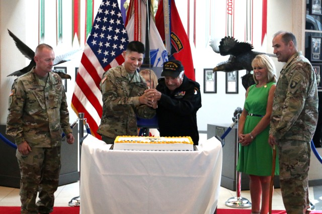 "Pvt. Mark Gurrola, human resources specialist, Headquarters and Headquarters Battalion, 101st Airborne Division, the youngest Soldier in the division at 18 years old, helps the oldest veteran of the 101st Vincent J. Speranza,  with Company H,  501st Parachute Infantry Regiment, 101st during WWII, cut the Birthday cake of the 101st's 75th Anniversary. Speranza spent the day with the 101st Soldiers celebrating 75 years of service to the country and is the author of ""Nuts!: a 101st Airborne Division Machine Gunner at Bastogne""."