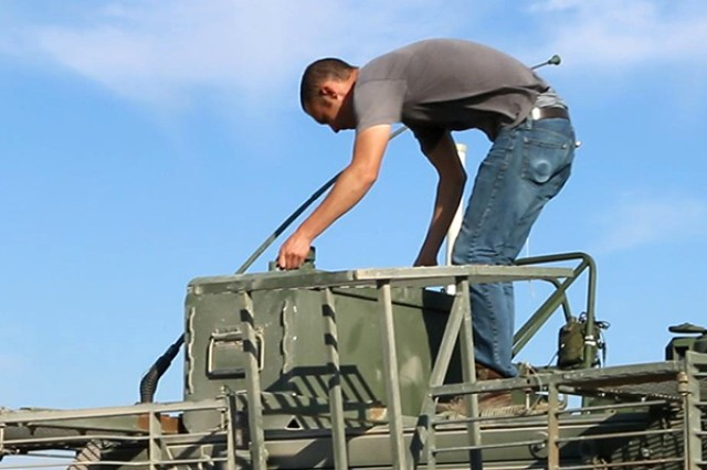 A technician prepares the Army's Stryker Nuclear, Biological, Chemical, Reconnaissance Vehicle for Joint Chemical Agent Detector system Stryker-On-The-Move tests at Target S Grid at Dugway Proving Ground, July 2017. The JCAD will be integrated with the Stryker vehicle as a replacement for the Automatic Chemical Agent Detection Alarm, which will no longer be manufactured for and fielded by the Army. Photo captured from video by Darrell L. Gray, Dugway Proving Ground Public Affairs.