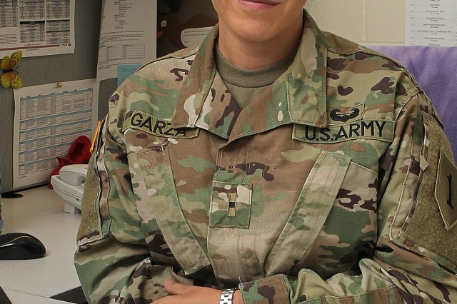 Warrant Officer Elida Garza, human resources officer, 1st Combat Aviation Brigade, 1st Infantry Division, sits at her desk in the CAB headquarters building Aug. 9 at Fort Riley, Kansas. (Chad L. Simon, 1st Inf. Div. Public Affairs)