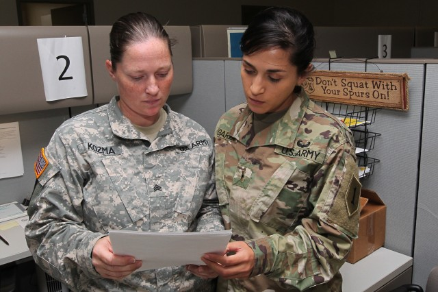 Warrant Officer Elida Garza, right, human resources officer, 1st Combat Aviation Brigade, 1st Infantry Division, reviews administrative paperwork with Sgt. Bevelyn Kozma, human resources noncommissioned officer, 1st CAB, 1st Inf. Div. Aug. 10 at Fort Riley, Kansas. (Chad L. Simon, 1st Inf. Div. Public Affairs)