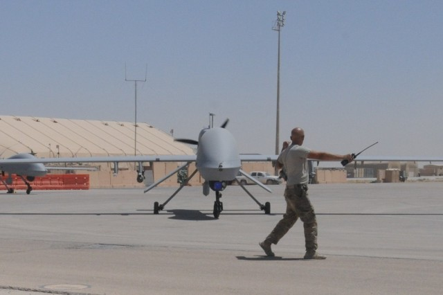AL ASAD AIR BASE, Iraq -- Spc. Jeremy Pratt, an unmanned aerial system repairer from Company D, 10th Aviation Regiment, 10th Mountain Division, guides a MQ-1C Gray Eagle Unmanned Aerial System into position following completion of a mission at Al Asad Air Base, Iraq, August 1,2017. The Gray Eagle provides reconnaissance, surveillance, target acquisition and an offensive strike capability for Combined Joint Task Force - Operation Inherent Resolve. CJTF-OIR is the Coalition to defeat ISIS in Iraq and Syria.