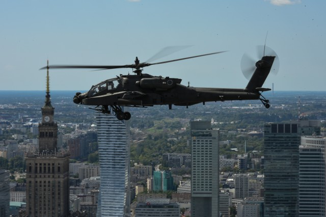 An AH-64 Apache Helicopter from 1st Battalion, 3rd Aviation Regiment, 12th Combat Aviation Brigade files past the Palace of Culture and Science over Warsaw, Poland, 15 Aug. 2017.  A UH-60 Black Hawk, CH-47 Chinook and an AH-64 Apache helicopter from the 12th CAB participated in the Polish Armed Forces Day parade to show solidarity and partnership with our long standing NATO ally.