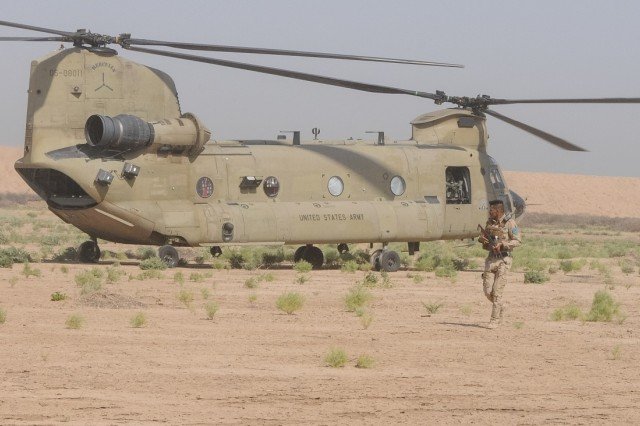 A member of the Iraqi Security Forces provides security for a CH-47 Chinook helicopter from the 2-149th General Support Aviation Battalion, Task Force Rough Riders during the aerial response force exercise at Camp Taji Military Complex, Iraq, August 13, 2017. This training is part of the overall Combined Joint Task Force - Operation Inherent Resolve building partner capacity mission which focuses on training and improving the capability of partnered forces fighting ISIS. CJTF-OIR is the global Coalition to defeat ISIS in Iraq and Syria. (US Army Photo by Capt. Stephen James)