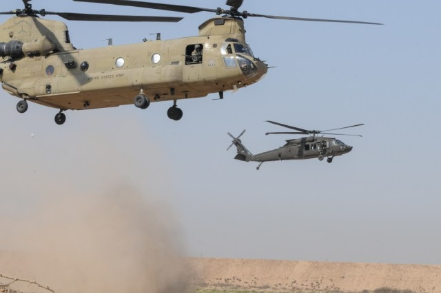 A UH-60M Black Hawk helicopter (right) and a CH-47 Chinook helicopter from 2-149th General Support Aviation Battalion, Task Force Rough Riders, lands prior to inserting Paratroopers from Task Force Red Falcon's Company C, 1st Battalion, 325th Airborne Infantry Regiment, 2nd Brigade Combat Team, 82nd Airborne Division, during the aerial response force exercise at Camp Taji Military Complex, Iraq, August 13, 2017.