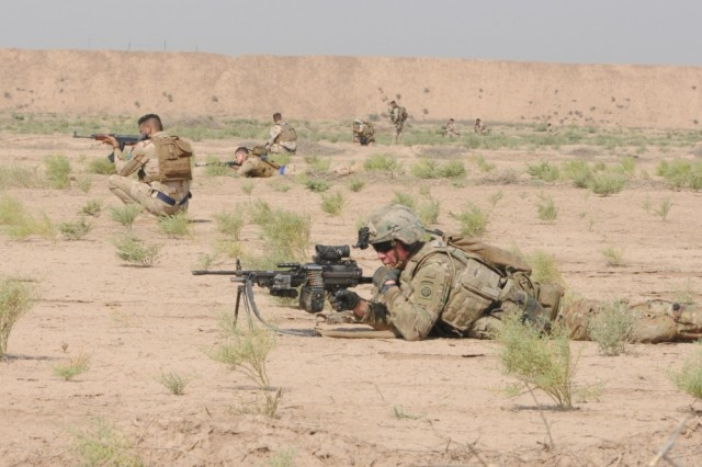 A paratrooper from Task Force Red Falcon's Company C, 1st Battalion, 325th Airborne Infantry Regiment, 2nd Brigade Combat Team, 82nd Airborne Division, and Iraqi Security Forces establish a security perimeter during the aerial response force exercise at Camp Taji Military Complex, Iraq, August 13, 2017.