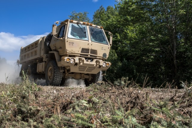 Soldiers from the 185th Engineer Support Company of the Maine Army National Guard drive their Light Medium Tactical Vehicle in a dump truck variant to their construction sites at Canadian Forces Base Gagetown, New Brunswick, Canada, August 17, 2017. The unit built a dual helicopter pad as well as a large sniper mound for their allies in the Canadian Forces. This effort is all part of the unit's annual training this year.
