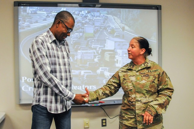 Army National Guard Maj. Kristina Murphy, National Guard Counterdrug Program Training branch chief, presents Errol, a police inspector from Suriname, with a Counterdrug Coin during the Disrupting Illicit Trafficking Networks course July 25 at the Northeast Counterdrug Training Center in Pennsylvania.