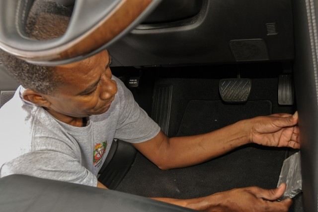 Errol, a police inspector from Suriname, removes a mock kilo of heroin from a hidden compartment in a car during the Disrupting Illicit Trafficking Networks course July 26 at the Northeast Counterdrug Training Center in Pennsylvania.