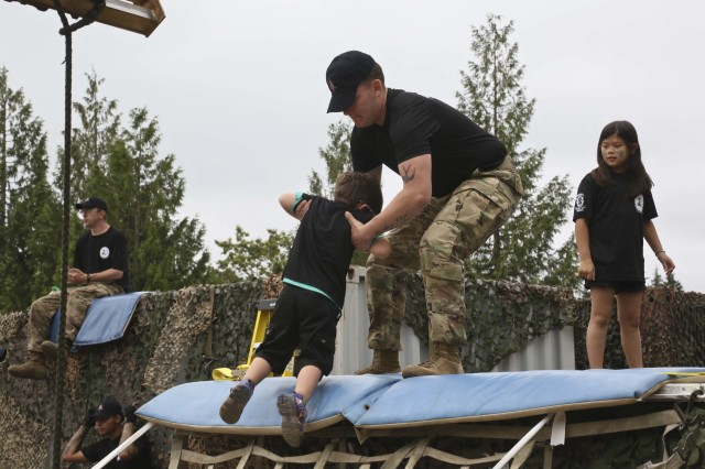 A Soldier from the 1st Special Forces Group (Airborne) assists a young boy to the top of an obstacle on Joint Base Lewis-McChord, Wa., on August 17. Children of all ages were allowed to participate in the Kids Q Course, an event that emulated their fathers' Special Forces Qualification Course.