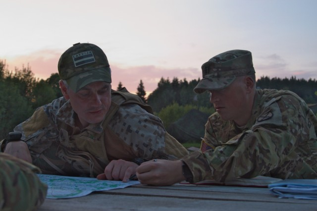 Army Capt. Zachary Johnston, assistant operations officer for 3rd General Support Aviation Battalion, 10th Aviation Regiment, 10th Combat Aviation Brigade, 10th Mountain Division, (left) and Latvian National Guard Capt. Marcis Slavinskis, a platoon leader with the Latvian 51st Infantry Battalion National Guard, (right) pour over local maps during Exercise Falcon's Talon near Jurmala, Latvia on August 18, 2017.