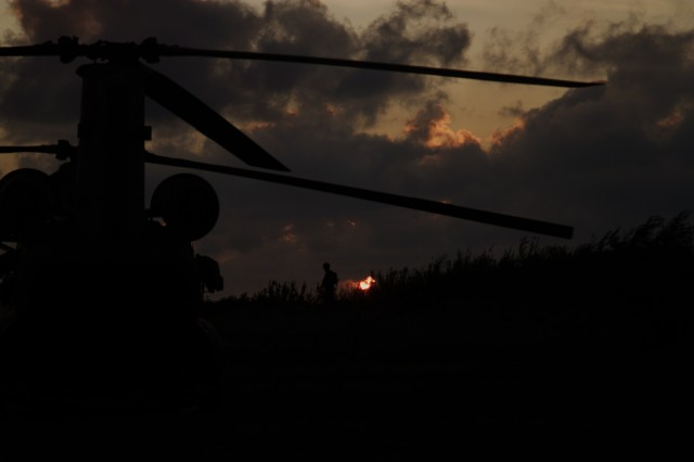 A U.S. Army Soldier with the 3rd General Support Aviation Battalion, 10th Aviation Regiment, 10th Combat Aviation Brigade, 10th Mountain Division, pulls security near a CH-47 Chinook during Exercise Falcon's Talon at Liepaja, Latvia on August 19, 2017.
