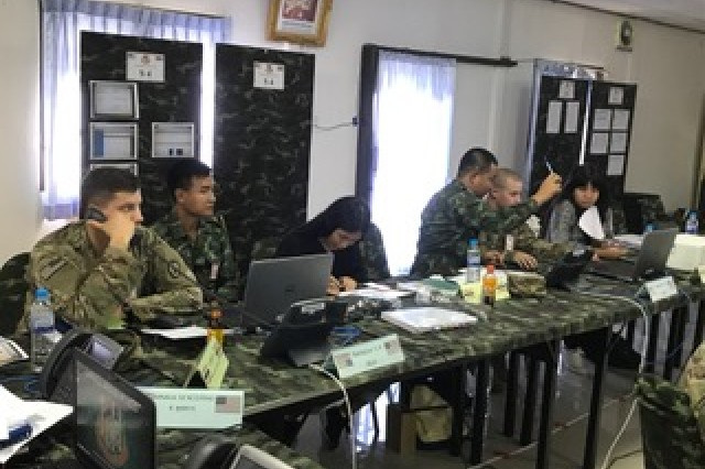 1st Lt. Nicholas Longaker (left) takes a phone call while Capt. Brian Erwin and his RTA counterpart review personnel statuses during the battalion STAFFEX at Fort Surasri, Thailand, Aug. 22, 2017.