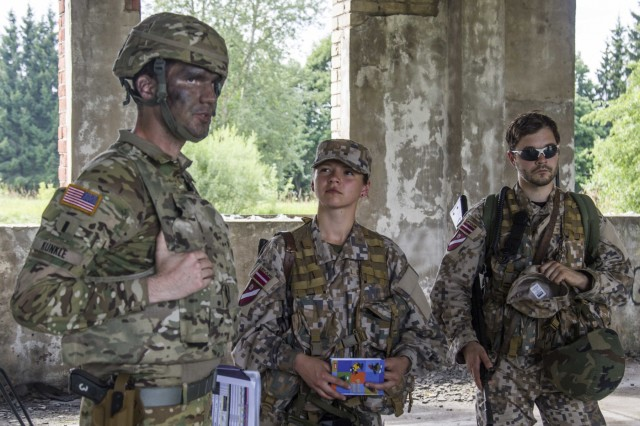 1st Lt. Adam Kunkle, a CH-47 Chinook pilot with B Company, 3-10 General Support Aviation Battalion, 10th Combat Aviation Brigade, discusses defenses strategies with Soldiers from the Latvian National Guard (Latviajas Republikas Zemessardze) on August 19 in Latvia. The two groups were building interoperability during Exercise Falcon's Talon with Latvian Soldiers offering their expertise and resources on the ground. (U.S. Army photo by Spc. Thomas Scaggs) 10821-A-TZ475-037
