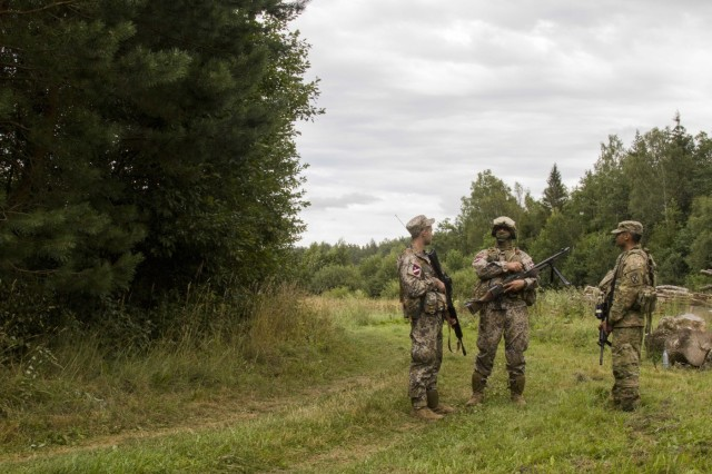 A Soldier from Task Force Baltic Phoenix, 3-10 General Support Aviation Battalion, 10th Combat Aviation Brigade, pulls security with Soldiers from the Latvian National Guard on August 21. The units were participating in Exercise Falcon's Talon, which seeks to develop new tactics, techniques, and procedures that will assist Army Aviation on a complex battlefield. (U.S. Army photo by Spc. Thomas Scaggs) 170821-A-TZ475-224