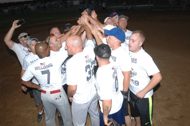 Members of the U.S. Marine Corps Detachment softball team celebrate after their 24-11 victory over the Air Force Det. in the championship game of the 2017 Commander's Cup Softball Tournament.