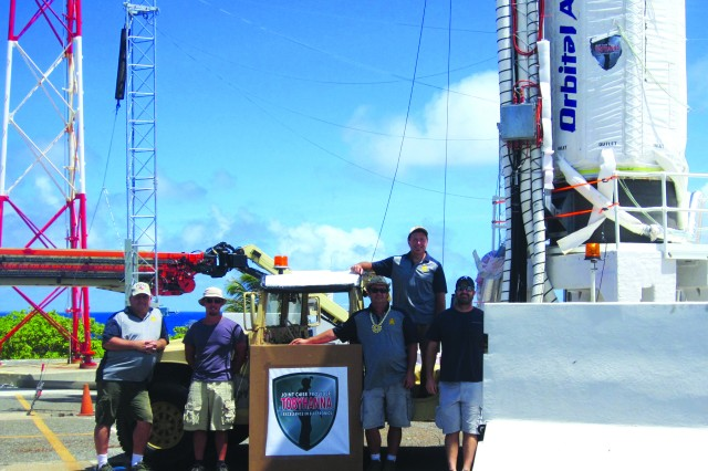 Tobyhanna Army Depot's Quality Engineer Leonard Zito (standing on Humvee) and Missile Defense Agency personnel stand next to a blast barrier on Launch Hill on the Kwajalein Atoll in the Republic of the Marshall Islands one day prior to launch. A launch stand was load tested up to 315,000 pounds to support the 106-foot-tall missile.