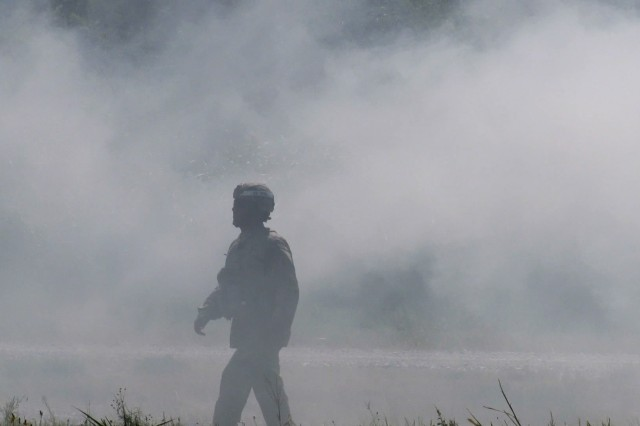 Drill Sergeant (Staff Sgt.) Diego Vega walks through concealing smoke watching the movements of C Battery, 1st Battalion, 79th Field Artillery Soldiers initiating an  attack during Field Training Exercise 3 here. Following the training, Vega quizzed his Soldiers on what they did right and what they did wrong.