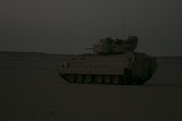An M2A3 Bradley Fighting Vehicle assigned to Bravo Company, 2nd Battalion, 7th Cavalry Regiment, 3rd Armored Brigade Combat Team, 1st Cavalry Division pulls area security in the tactical assembly area at Udairi Range Complex prior to conducting an early morning attack on the opposing forces during the company's situational training exercise Aug. 1, 2017. The STX was used to validate the unit through mission essential tasks to sustain the readiness of the combined arms battalions.