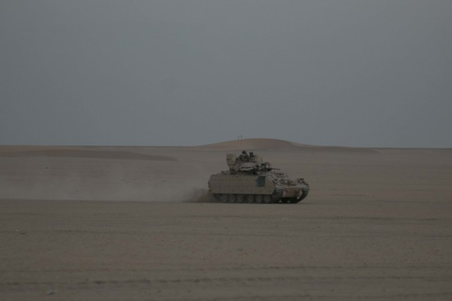 An M2A3 Bradley Fighting Vehicle assigned to Bravo Company, 2nd Battalion, 7th Cavalry Regiment, 3rd Armored Brigade Combat Team, 1st Cavalry Division maneuvers through Udairi Range Complex during an early morning attack on the opposing forces as a part of the company's situational training exercise Aug. 1, 2017. The STX provided an opportunity for Soldiers to conduct maneuver training and build confidence in their weapon systems and skill sets.