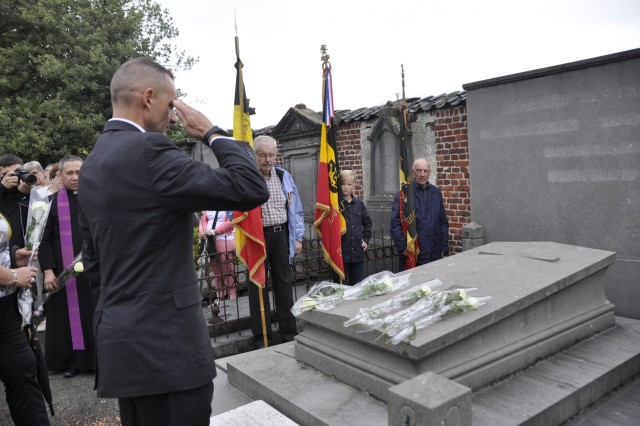 Garrison Chaplain Lt. Col. William Lovell (left) saluted Belgian Air Force Lt. Col. Joseph Daumerie after laying a rose on his grave during a commemoration event Aug. 15, 2017, in Brugelette, Belgium. Lovell later spoke about the importance of Daumerie's sacrifice and the solidarity between the American and Belgian communities.
