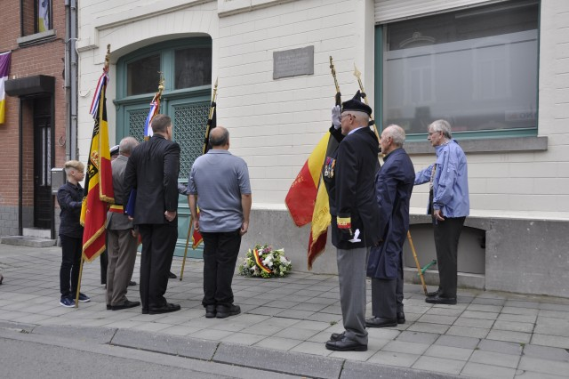 Before heading to the reception, attendees gathered around Daumerie's memorial plaque at the local pharmacy, where he was born, and placed a wreath beneath it Aug. 15, 2017 in Brugelette, Belgium. The garrison chaplains joined the local community in honoring the 75th anniversary of Daumerie's death.