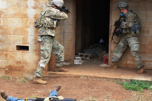 After eliminating an enemy combatant role player, Soldiers search a building as part of Squad Overmatch training at Schofield Barracks, Hawaii. During live training, Soldiers dealt with IEDs, snipers, suicide bombers, and civilian and military casualties. (U.S. Army photo by Mike Casey)