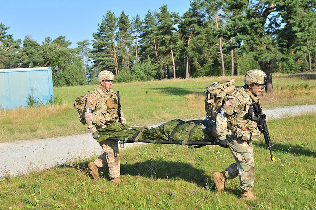 1st Lt. Christopher Finseth (left), and Sgt. Jonathan Renteria, both with U.S. Army Africa, carry a litter with a dummy to an awaiting helicopter on the medical evacuation portion of the buddy run at the 2017 European Best Warrior competition Aug. 23 at Grafenwoehr Training Area, Germany.Renteria was named 2017 U.S. Army Europe Noncommissioned Officer of the Year.