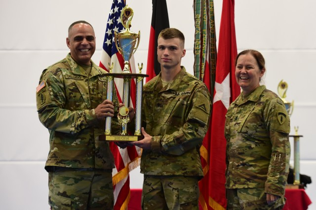GRAFENWOEHR, Germany - U.S. Army Europe Command Sgt. Maj. Sheryl D. Lyon (right) and 21st Theater Sustainment Command Command Sgt. Maj. Alberto Delgado present 2017 European Best Warrior, Soldier to Spc. Jacob Henriksen, 7th Army Training Command. Twenty-two Soldiers, noncommissioned officers, warrant officers and officers from units across the European theater and U.S Army Africa converged August 20 - 25 to compete in U.S. Army Europe's 2017 European Best Warrior Competition, in Grafenwoehr, Germany, where they faced a five-day barrage of mental, physical, and tactical trials to test their skills and resiliency.