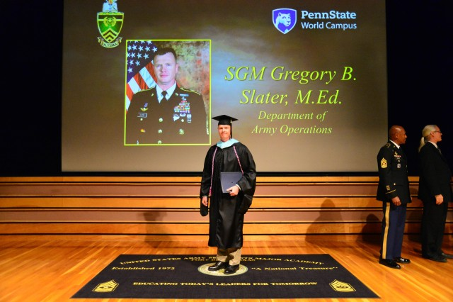 Sgt. Maj. Gregory B. Slater poses in front of his picture during the graduation celebration Aug 22 which saw him receive his certificate of completion for a Master's Degree in Lifelong Learning and Adult Education from Pennsylvania State University's World Campus.  Slater joined 19 other sergeants major who made up Cohort #2 of the U.S. Army Sergeants Major Academy Fellowship Program.