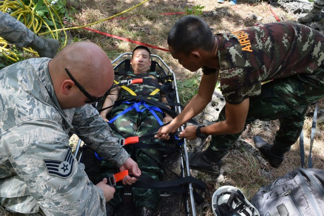 Staff Sgt. Derek Reese, Heavy Equipment Operations Craftsman, 141 Civil Engineer Squadron of the Washington Air Nation Guard search and rescue team ensures the lines are tight on the hoist with a soldier of the Royal Thai Army search and rescue team during Exercise Hanuman Guardian 17 in Fort Surasri, Thailand, Aug. 23, 2017.