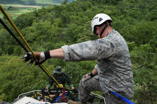 Tech. Sgt. Michael Cohan, a HVAC craftsman of the 141st Civil Engineer Squadron in the Washington Air National Guard Search and Rescue team mans the lines for soldiers of the Royal Thai Army's search and rescue team as they lower a simulated casualty down a cliff face during Exercise Hanuman Guardian 17 in Fort Surasri, Thailand, Aug. 23, 2017.