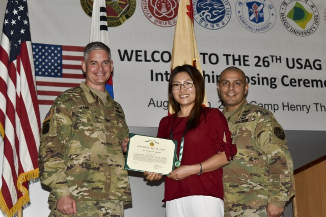 (From left to right) Col. Robert P. Mann Jr., USAG Daegu commander and Command Sgt. Maj. Juan A. Abreu present the outstanding intern supervisor award to Sin, Hyon-chong, management analyst from USAG Daegu Plans, Analysis, Integration Office, Aug. 18, at the Camp Henry Theater.