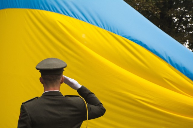 A Ukrainian soldier salutes his country's flag during a Ukrainian Independence Day celebration in Yavoriv, Ukraine, on Aug. 24. (Photo by Spc. Samuel Mason, 45th Infantry Brigade Combat Team)