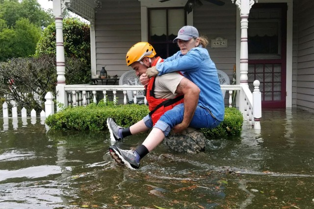 A Texas National Guardsman carries a resident from her flooded home following Hurricane Harvey in Houston, Aug. 27, 2017.