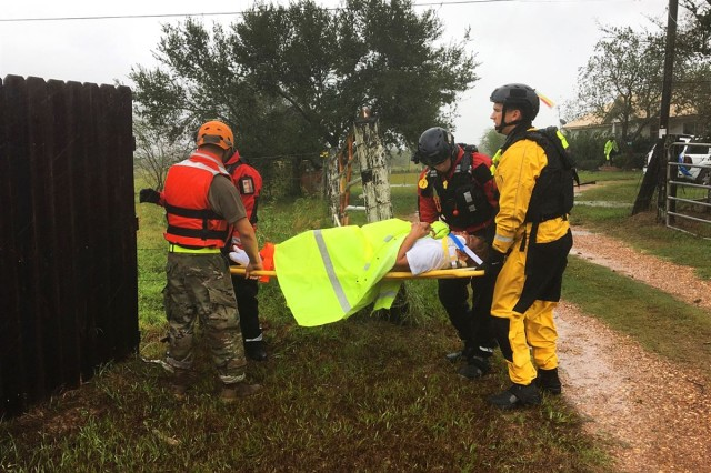 Texas National Guardsmen work with emergency responders by evacuating a resident on a stretcher affected by Hurricane Harvey during search and rescue operations near Victoria, Texas, Aug. 27, 2017.