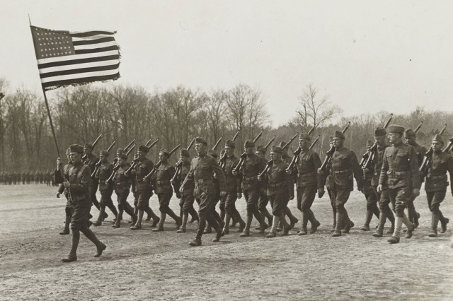 "Soldiers of the 77th Division parade the United States flag during a ""blessing the colors"" ceremony at Camp Upton in Yaphank, New York in 1918. The division was composed of draftees recruited mainly from the New York City area. ( Library of Congress Photo)"