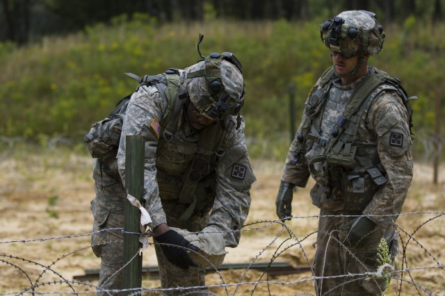 Pfc. Leroy King, left, and Sgt. Bradly Peterson, both assigned to a combat engineer assigned to 396th Engineer Company, Mobility Augmentation Company, construct a barbed wire barrier during Combat Support Training Exercise 86-17-02, Aug. 17, 2017, on Fort McCoy, Wis. CSTX is a 181st Infantry Brigade led, 4th Cavalry Multi-Functional Training Brigade supported exercise designed to assist combat-service and combat-service-support units in planning, preparing, supervising and executing of pre-mobilization collective training.