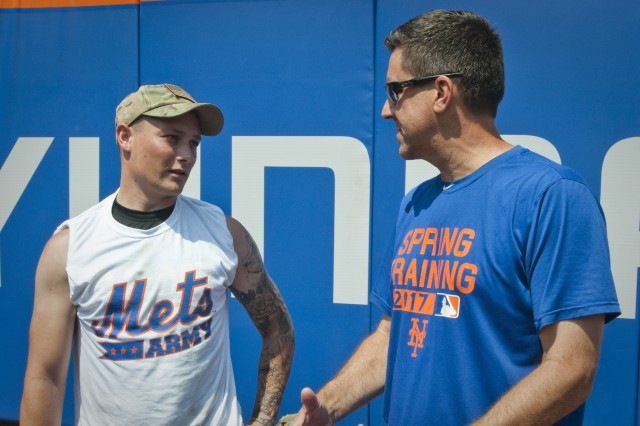 New York City Army softball team shortstop David Jensen speaks with New York Mets bench coach Dick Scott during a lull in action during the 3rd annual Mets Military Softball Classic Aug. 21, 2017 at Citi Field in New York City. Jensen, an Army staff sergeant, is a recruiter with the U.S. Army's New York City Recruiting Battalion. (U.S. Army photo by Master Sgt. Jeremy Crisp/Released).